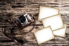 减速火箭的照相机和空白的照片框架在木桌上 顶视图 免版税库存图片