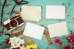 减速火箭的照相机和空的老立即纸象册在木桌上与花边界设计 库存照片