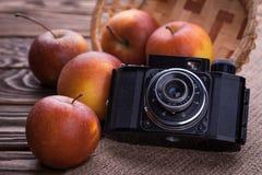 减速火箭的照相机和红色苹果在木桌上 库存照片