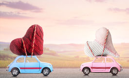 减速火箭的玩具汽车夫妇有华伦泰心脏的 免版税库存照片
