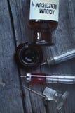 减速火箭的瓶和注射器在木背景 库存图片