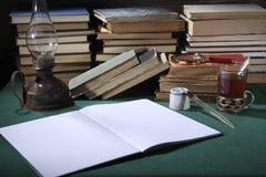 减速火箭的生活仍然 在桌面上,有:煤油灯、滴漏、笔杆、老墨水瓶和旧书 免版税库存图片