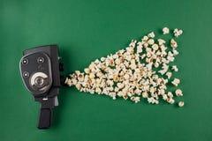 减速火箭的电影摄影机用飞行在它外面的玉米花在绿色背景 免版税库存图片