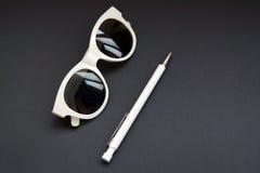 减速火箭的白色太阳镜和笔在黑桌上 库存照片