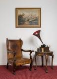减速火箭的皮革扶手椅子,老留声机,在圆的咖啡桌上的圆筒 免版税图库摄影