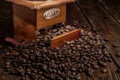 减速火箭的磨咖啡器用在黑暗的土气背景的咖啡粒 库存图片