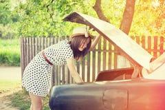 减速火箭的站立在汽车旁边的样式少妇 免版税图库摄影
