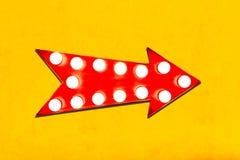 减速火箭的红色箭头塑造了与发光的电灯泡的葡萄酒五颜六色的被阐明的金属显示方向标在生动的黄色墙壁上 免版税库存图片