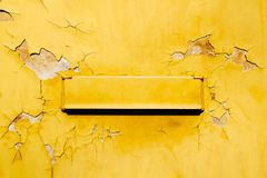 减速火箭的老黄色邮箱葡萄酒邮政箱子在破裂,难看的东西和剥登上了黄色墙壁 免版税库存照片