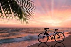 减速火箭的自行车剪影在沙滩的 库存照片