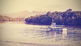 减速火箭的葡萄酒过滤了一条小船的图片在Krabi河的 免版税图库摄影