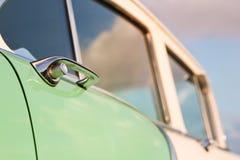 减速火箭的葡萄酒绿色和白色汽车 里面门把手 汽车大于1985年 免版税库存照片