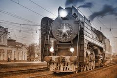 减速火箭的蒸汽火车在驻地站立在晚上时间 库存照片