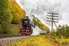 减速火箭的蒸汽火车接近山 免版税库存照片