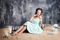 减速火箭的蓝色礼服的可爱的妇女有蜡烛和镶边枕头的 库存图片