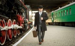 减速火箭的衣服的人带着手提箱走在火车平台的 免版税库存图片