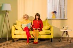 减速火箭的衣物看书的妇女坐黄色沙发在明亮的公寓玩偶 库存图片