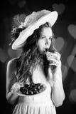 减速火箭的衣裳的吃巧克力的年轻美丽的妇女黑白色摄影  免版税库存图片