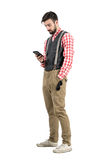 减速火箭的衣裳的轻松的年轻人键入在智能手机的消息 库存图片