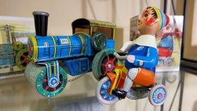 减速火箭的金属玩具火车和圣诞节矮子骑马骑自行车 免版税库存照片