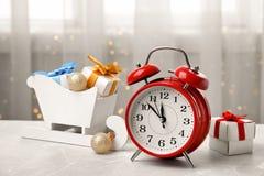减速火箭的闹钟、礼物和欢乐装饰在桌上 免版税库存图片