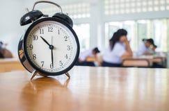 减速火箭的闹钟特写镜头有十个o `时钟的在桌老师我 库存图片