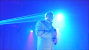 减速火箭的音乐会被弄脏的背景 资深唱歌入话筒的一个老人 明亮慢动作录影的光 股票视频