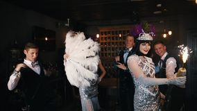 减速火箭的题材党-获得的年轻人乐趣-拿着一个巨大的瓶与烟花的香槟的妇女在上面 股票视频