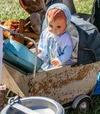 减速火箭的婴儿车和玩偶显示在车库售物 免版税库存图片