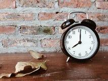 减速火箭的黑闹钟和烘干在木桌上的叶子 库存照片