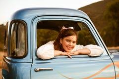 减速火箭的20世纪50年代青少年在经典蓝色卡车 免版税库存照片