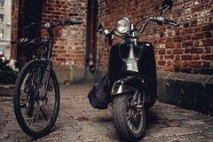 减速火箭的moto滑行车和黑自行车 免版税库存照片