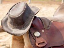 减速火箭被称呼的皮革马鞍和车手皮革帽子 图库摄影