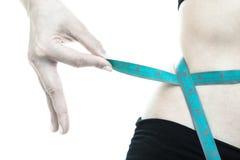 减重。在妇女身体的蓝色测量的磁带 免版税图库摄影