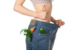 减重和健康吃的或节食的概念 过大的牛仔裤的亭亭玉立的女孩有在口袋的未加工的蔬菜的 图库摄影