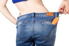 减重和健康吃的或节食的概念 过大的牛仔裤的亭亭玉立的女孩用在口袋的一棵红萝卜 库存照片