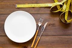 减重概念的饮食 适当的营养 医疗饥饿 有叉子和刀子近的测量的磁带的空的板材 库存照片