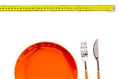 减重概念的饮食 适当的营养 医疗饥饿 有叉子和刀子近的测量的磁带的空的板材 库存图片