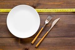 减重概念的饮食 适当的营养 医疗饥饿 有叉子和刀子近的测量的磁带的空的板材 免版税库存照片