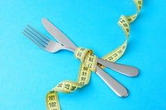 减重的低卡路里食物 叉子和刀子在蓝色的黄色测量的磁带被包裹 免版税图库摄影