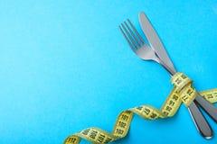 减重的Paleo饮食 叉子和刀子在蓝色的黄色测量的磁带被包裹 免版税库存图片