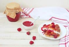 凝乳布丁片断用在白色板材的山莓果酱 库存照片