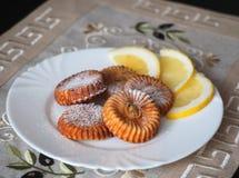 凝乳饼干和一些个切片在白色板材的柠檬 免版税库存图片