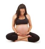 凝思姿势怀孕的供以座位的女子瑜伽 免版税库存照片