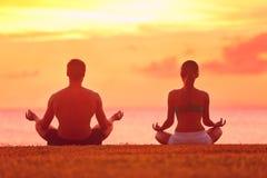 凝思思考在海滩日落的瑜伽夫妇 免版税库存照片