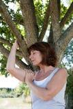凝思的年轻老化妇女与复活的一棵树 库存图片