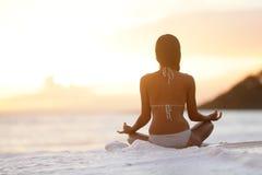 凝思-思考在海滩日落的瑜伽妇女 库存图片