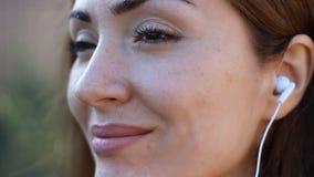 凝思 放松 在微笑的耳机和听的音乐的妇女特写镜头 股票视频