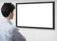 凝视与黑屏的电视的商人 免版税库存图片
