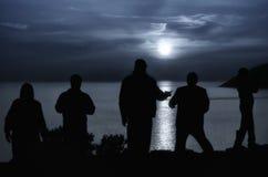 凝视发光在海的月亮的人们 库存图片